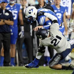 Taysom Hill (4) of the Brigham Young University Cougars is injured as he is tackled by Brian Suite (21) of the Utah State Aggies during NCAA football in Provo, Friday, Oct. 3, 2014.
