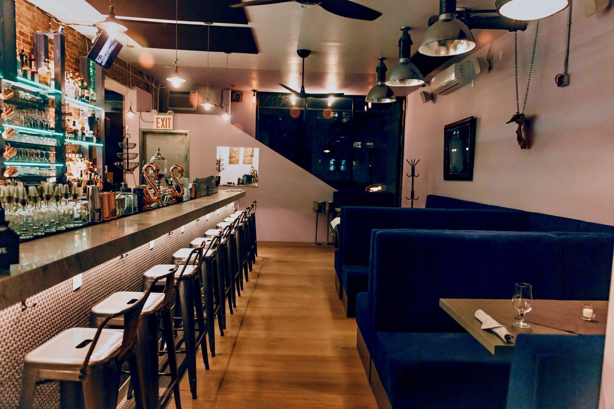 An interior shot displaying a backlit bar to the left and dark booths for sit-down dining on the right