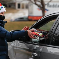 Lacey Cole-Rae hands hats and gloves to a recipient during the Big Brothers Big Sisters Holiday Drive Thru at a parking lot in Taylorsville on Thursday, Dec. 10, 2020.During the event, Littles (youth living in adversity), their Bigs (Volunteer Mentors) and their families were invited to pick up warm winter coats, gift cards and fun treats.