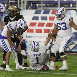 Brigham Young Cougars quarterback Zach Wilson (1) is helped up after scoring against the UCF Knights during the Boca Raton Bowl in Boca Raton, Fla., on Tuesday, Dec. 22, 2020.