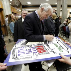 Republican presidential candidate Rep. Ron Paul, R-Texas, autographs a poster at a caucus site at Shawnee Mission Northwest High School  Saturday, March 10, 2012, in Shawnee, Kan.
