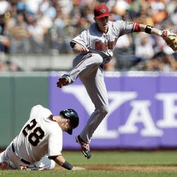 Arizona Diamondbacks second baseman Aaron Hill watches his throw to first after forcing out San Francisco Giants' Buster Posey on a ground ball by Hunter Pence during the third inning of a baseball game Thursday, Sept. 27, 2012, in San Francisco. Pence was out at first.