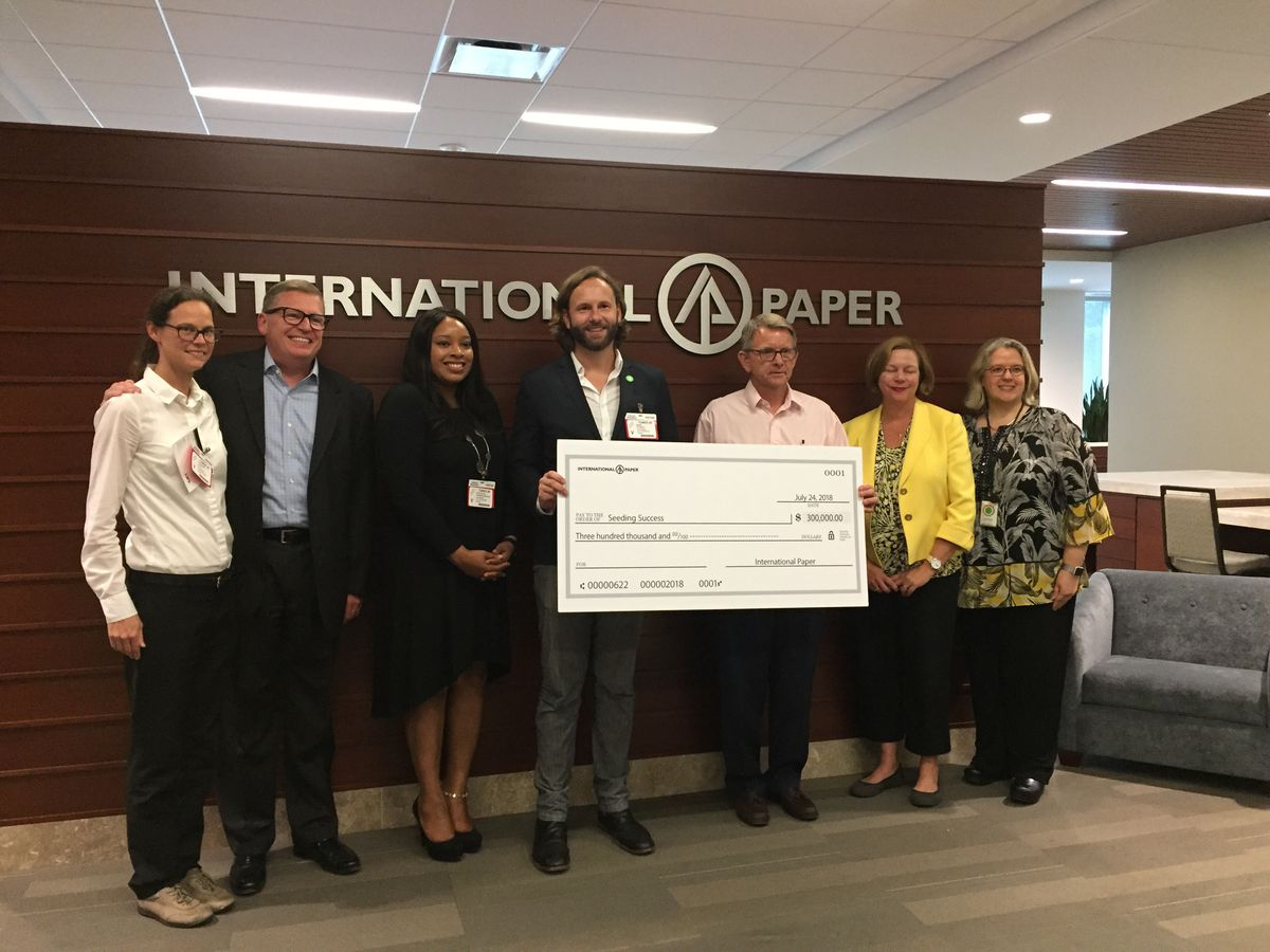 Seeding Success and International Paper leaders pose with a check for $300,000.