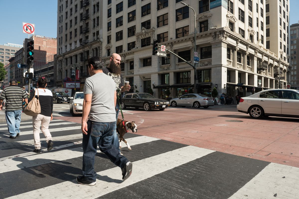 Men and women walk in a marked crosswalk with a tall old building in the background.