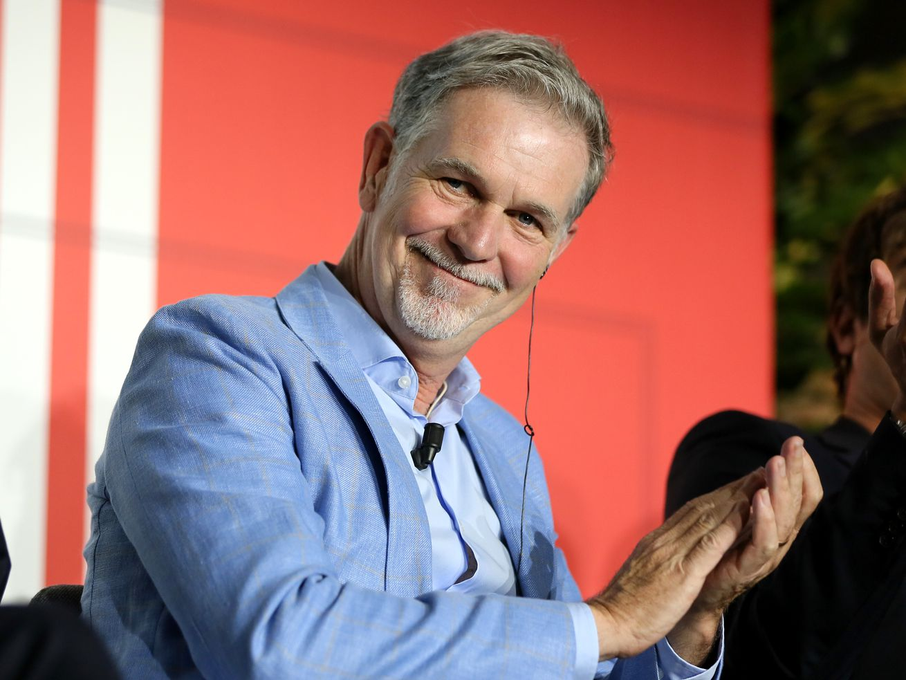 Netflix CEO Reed Hastings smiling and applauding from his seat onstage