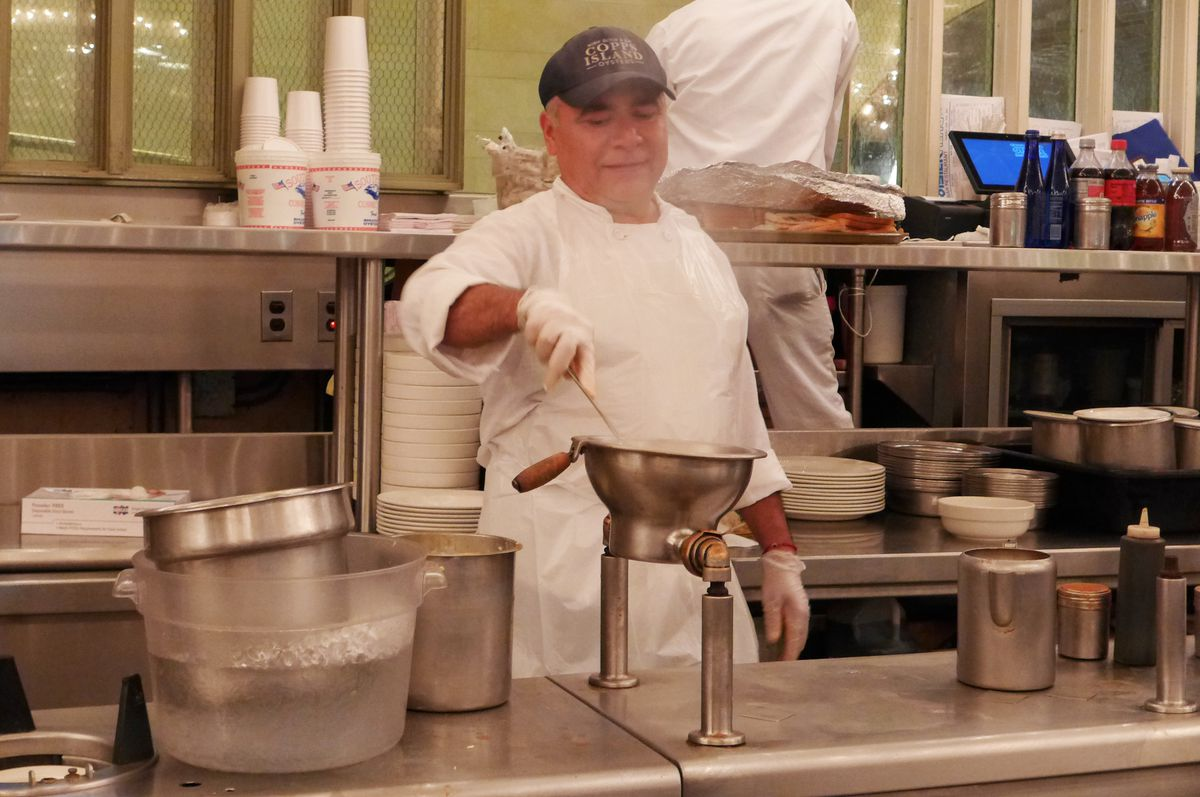 A white aproned cook in a baecall cap stands behind a steaming kettle with a hand that can be turned over to pour out soup...