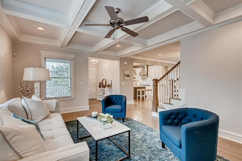 A white and beige living room with blue and white furniture.