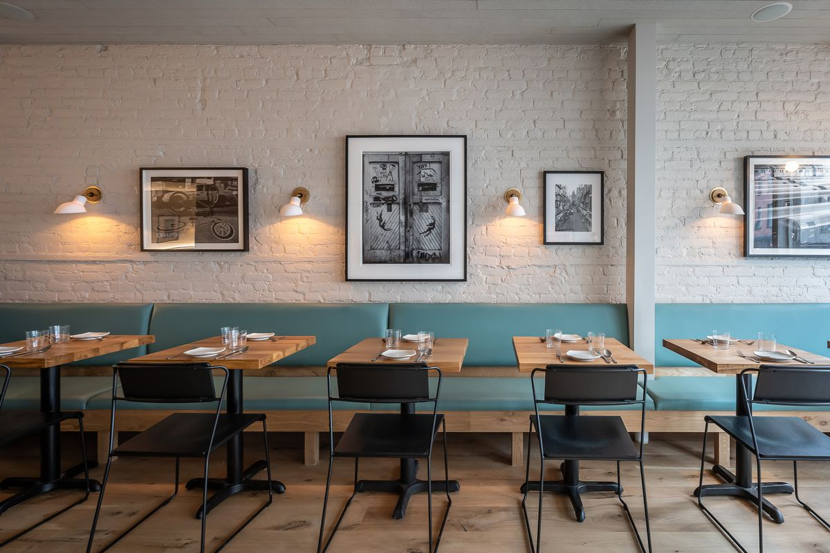 The Banty Rooster's dining room with light blue banquettes and whitewashed brick walls