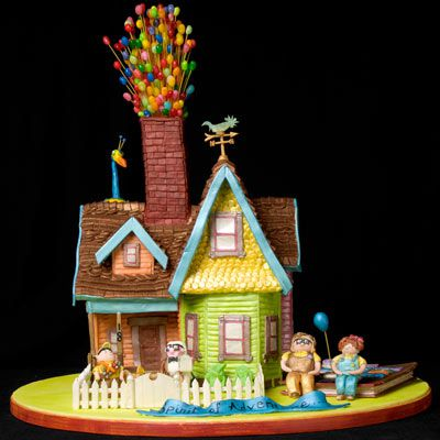 Gingerrbread house with a chimney with balloons sticking out of it made of jelly beans on dried spaghetti.