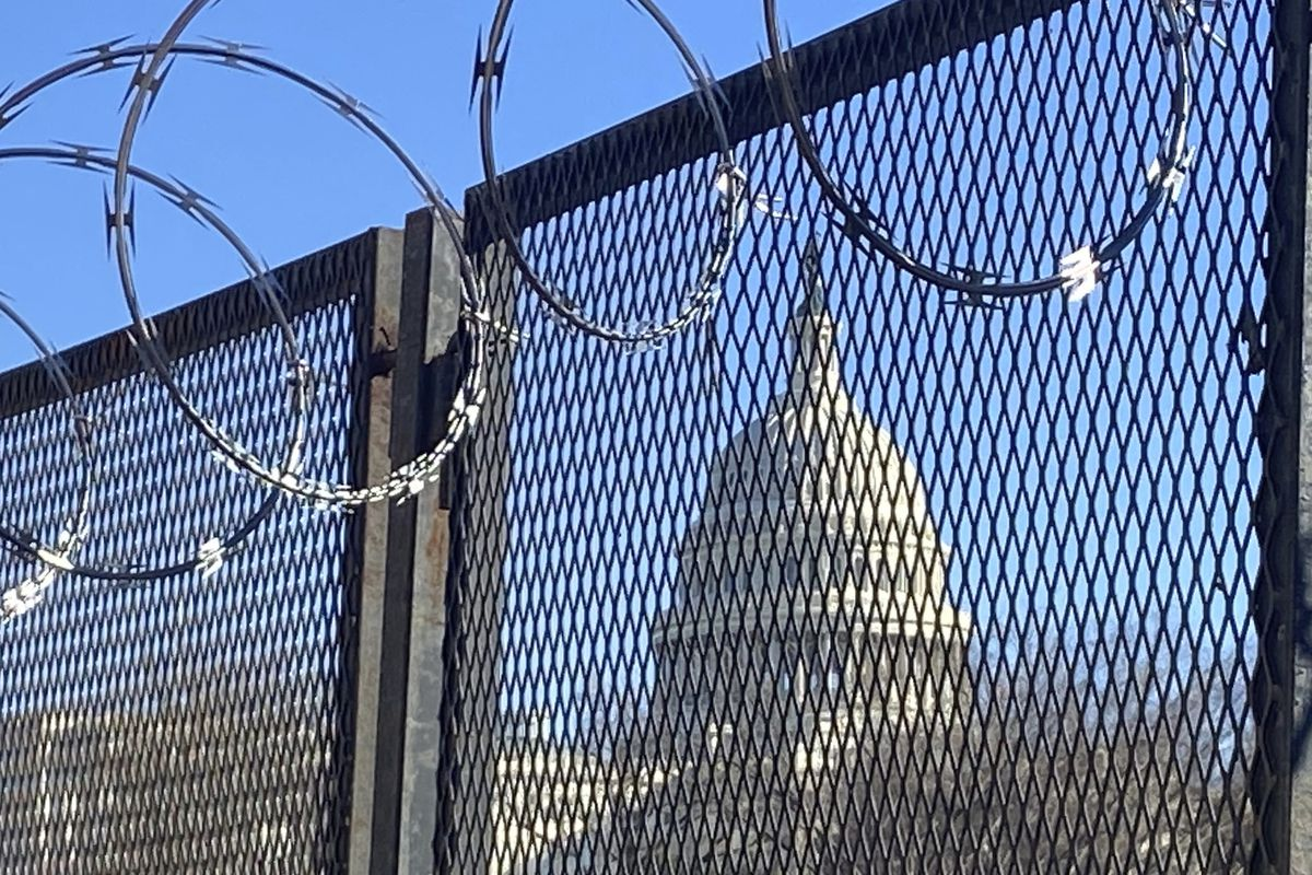 In this Saturday, Jan. 23, 2021 photo, riot fencing and razor wire reinforce the security zone on Capitol Hill in Washington.