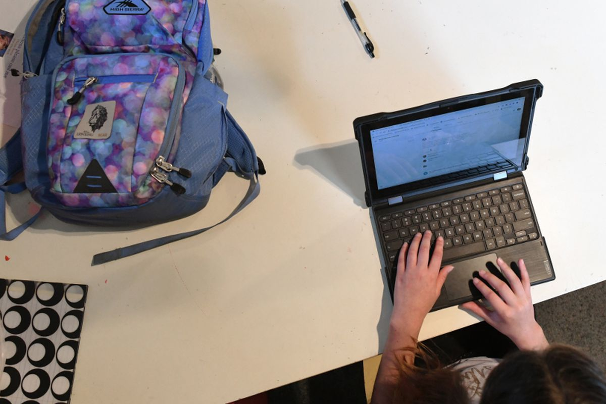 A student works on a laptop at home with her backpack next to her.