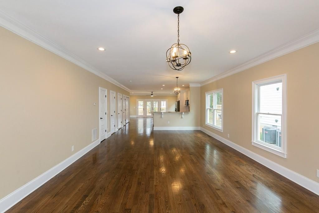 Empty open floorplan with living area in foreground and kitchen in the background.