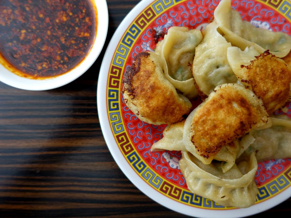 From above, a decorative plate containing a pile of dumplings beside a small bowl of chile sauce
