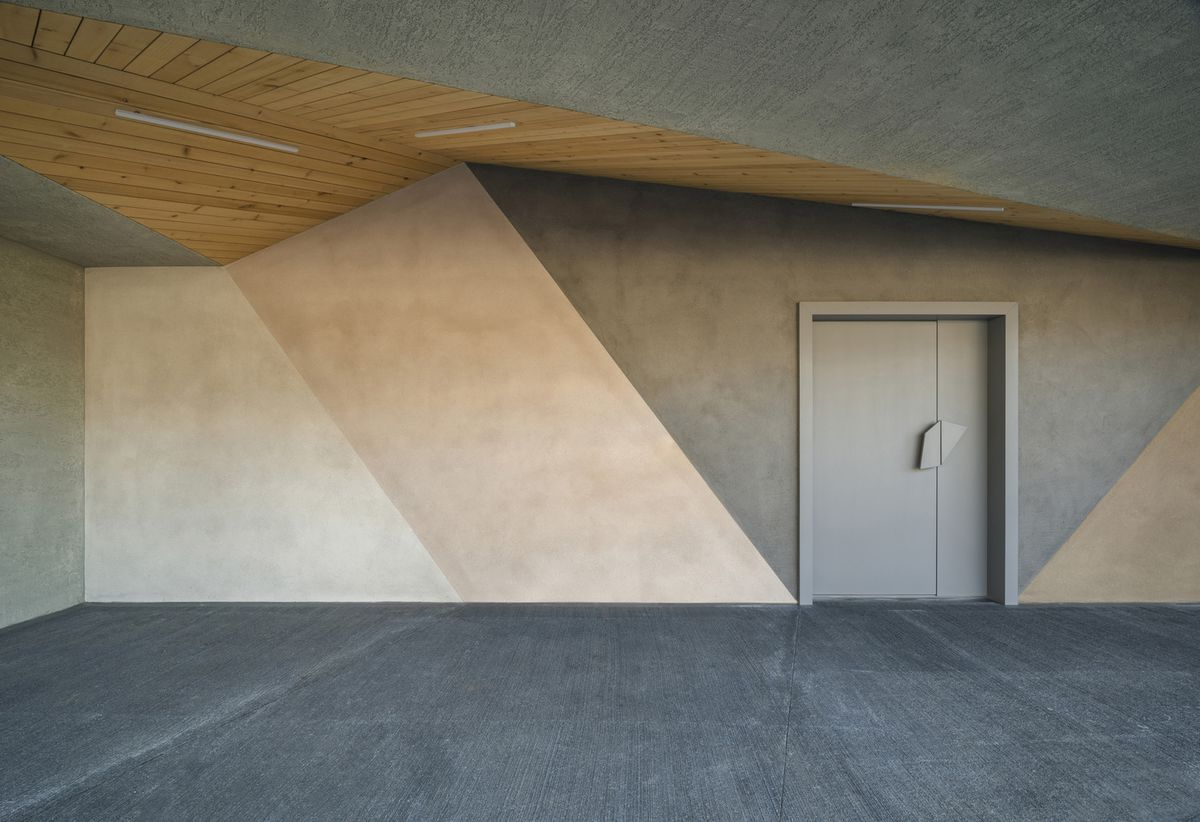 The exterior of a concrete house. The concrete is dyed pink, ivory, and grey.