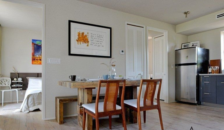 A dining area. There is a table and chairs. Against the far wall is a silver refrigerator and blue cabinetry.
