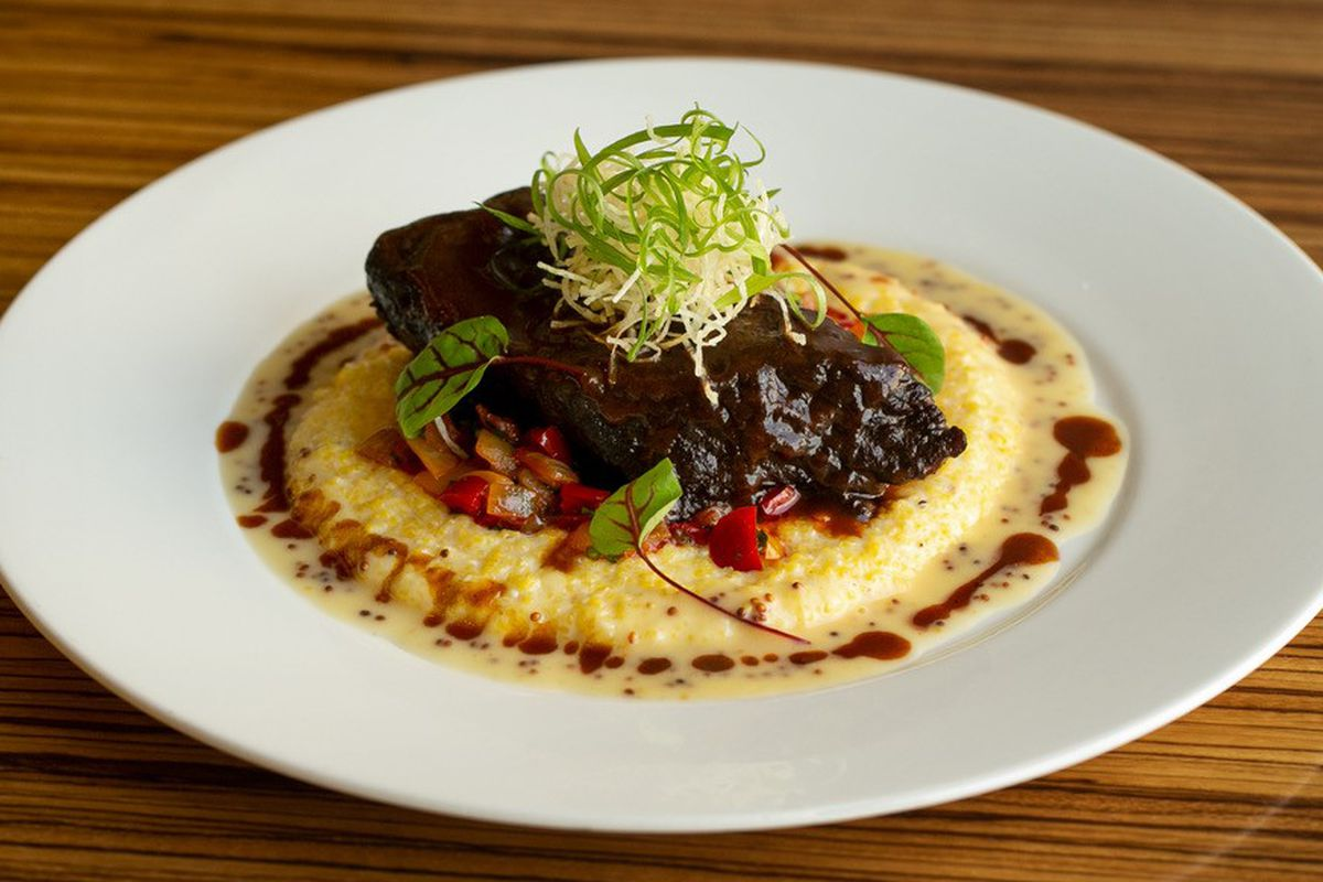 A plate of tamarind glazed angus short rib with Wade's mill corn grits, ratatouille, crispy taro, and Ghent mustard emulsion.