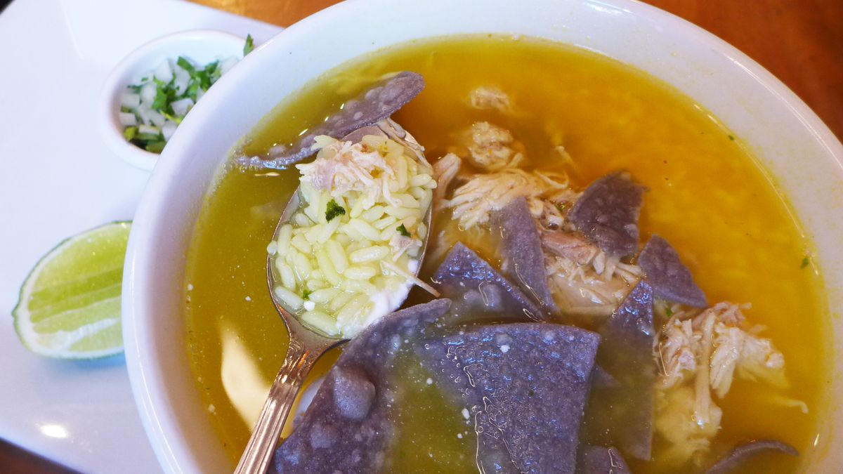 A round bowl of very yellow soup floating dark blue corn chips, with lime and chopped onions on the side.