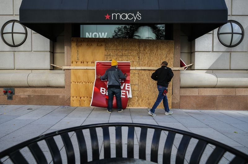 Pedestrians on the sidewalk outside a boarded-up entrance to Macy's.