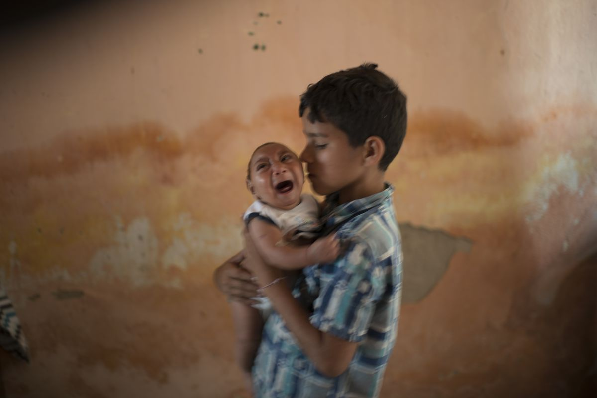 A 10-year-old boy nurses his 2-month-old brother, who was born with microcephaly in Poco Fundo, Pernambuco state, Brazil.