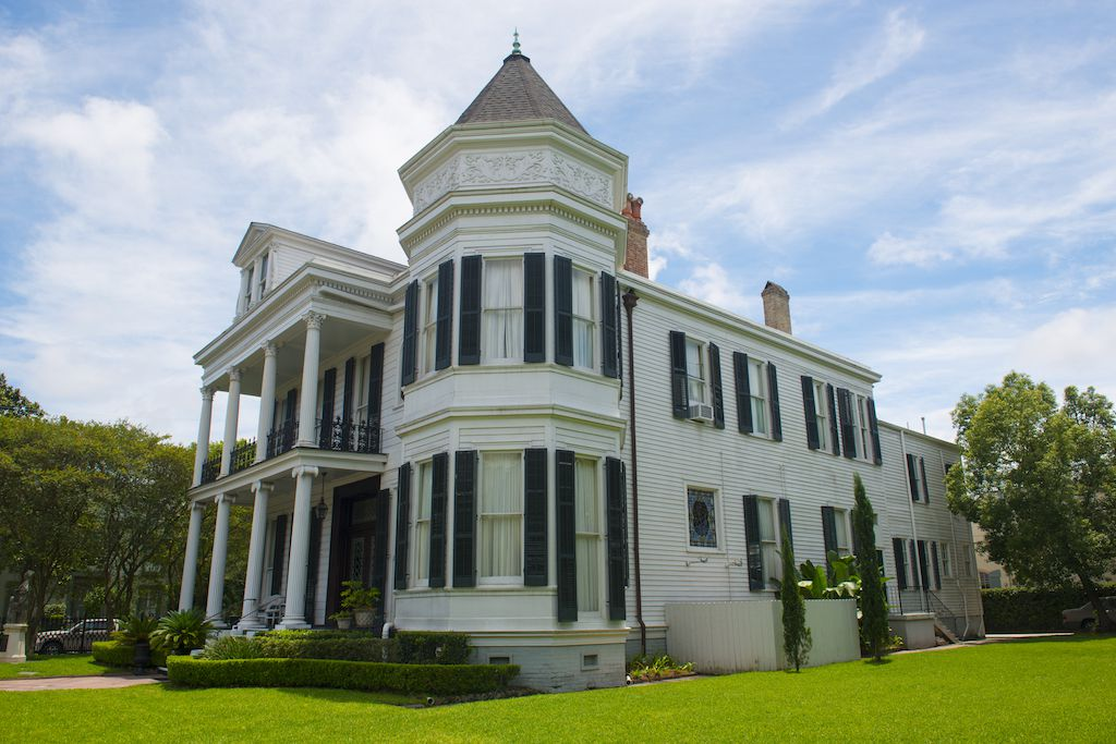 A large house with a white facade and black shutters. There are columns in the front of the house near the entrance.