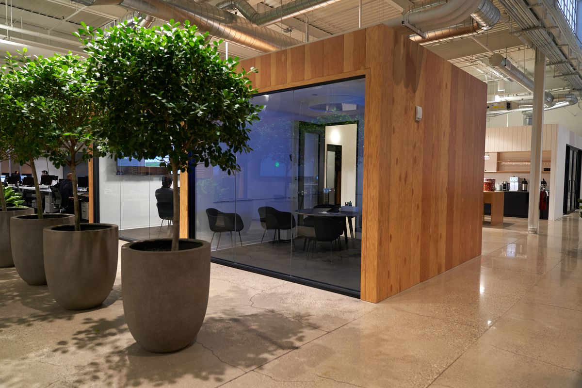 A square room in the middle of a large space. There's polished concrete floors and a couple large planters nearby.