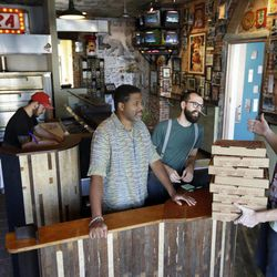 In this Wednesday, Sept. 12, 2012 photo, the owners of Pizza Brain, from left, Joseph Hunter, Michael Carter, Ryan Anderson, and Brian Dwyer work the storefront in Philadelphia.  Hundreds of people turned out for the grand opening of Pizza Brain this month in Philadelphia's Fishtown neighborhood. It's a restaurant where visitors can eat a slice or two of artisan pie while gawking at a pizza-related photos, records, knickknacks and videos. Though only a portion of the massive collection is on display, Dwyer says the items will be rotated so there's always something new to see.