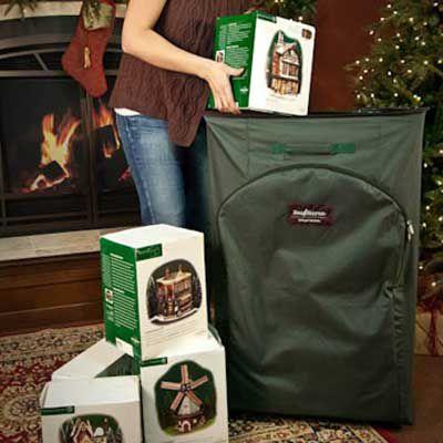 Uma grande caixa verde para decoração de Natal na frente de uma árvore de Natal.