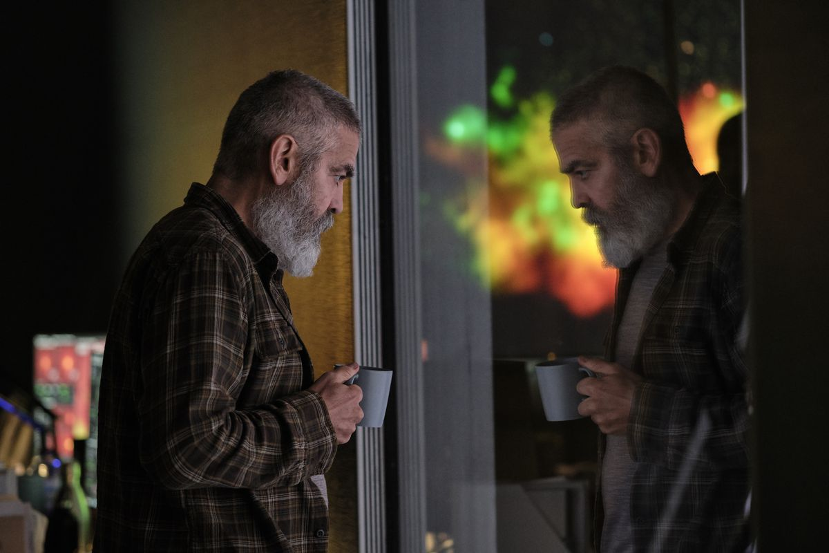 george clooney holding a cup of coffee and looking out at some spacey window in