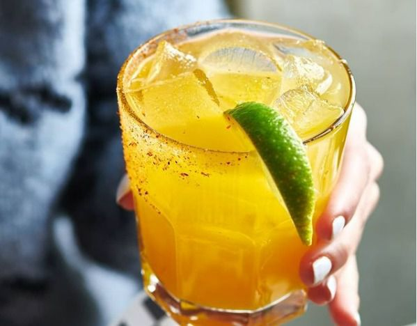 A hand with painted fingernails holds an orangish iced cocktail with a lime wedge.