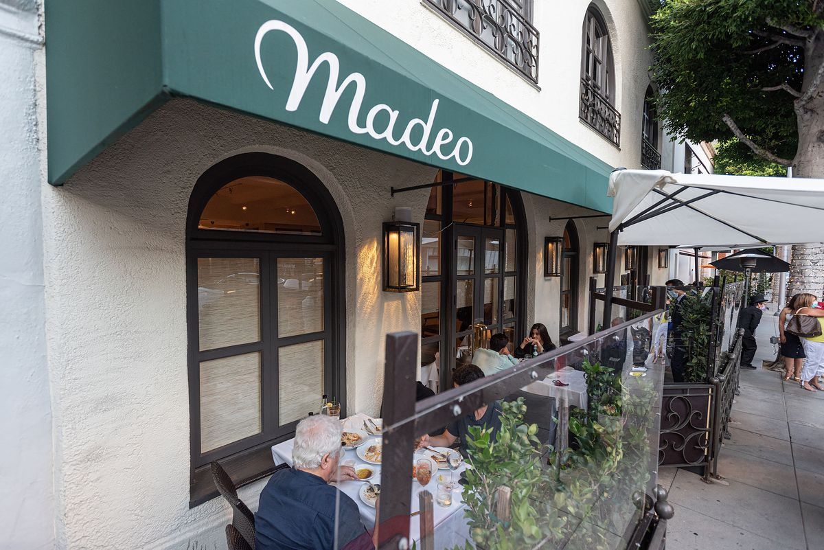 A green awning shows the name Madeo as diners sit behind Plexiglas.