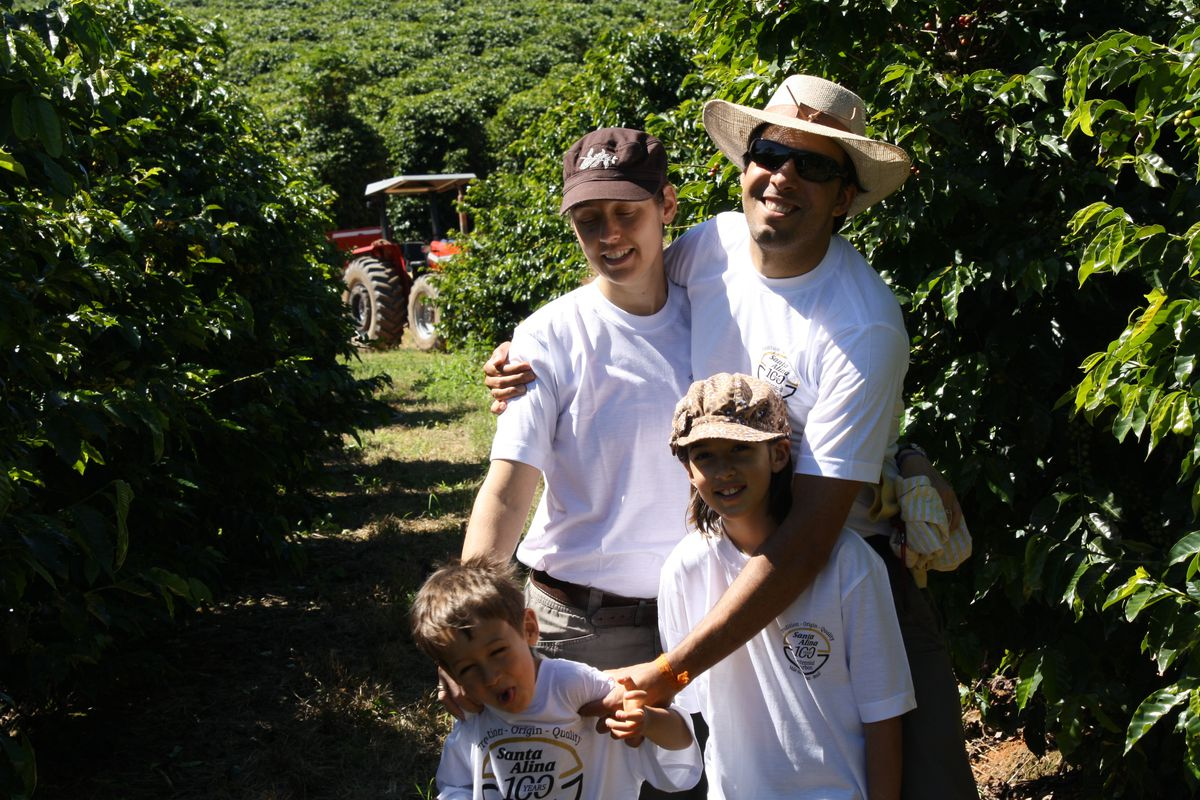 A man holds his two kids and wife among the coffee plants in Brazil.