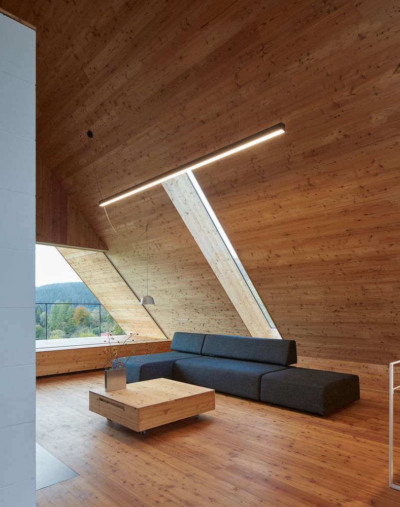 Gray sofa in a wooden cabin with vaulted ceilings.