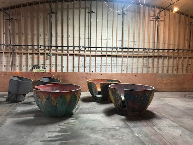 Three concrete teacup-shaped booths in a space under construction.