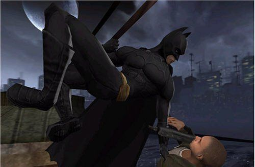 Batman hangs from above while holding a guy with a gun