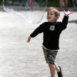 Dylan Cruz reaches for a Monster Bubble at the Downtown Farmers Market at Pioneer Park in Salt Lake City on Saturday, June 14, 2014.