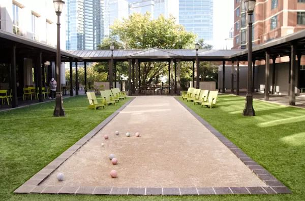 A bocce ball court in the middle of a green lawn.