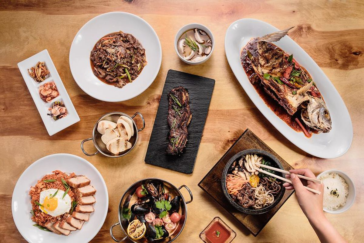 An array of dishes and trays with food from Jenna's Asian Kitchen, from rice and sliced meats to toasted breads to a whole fish, to someone picking up food with chopsticks
