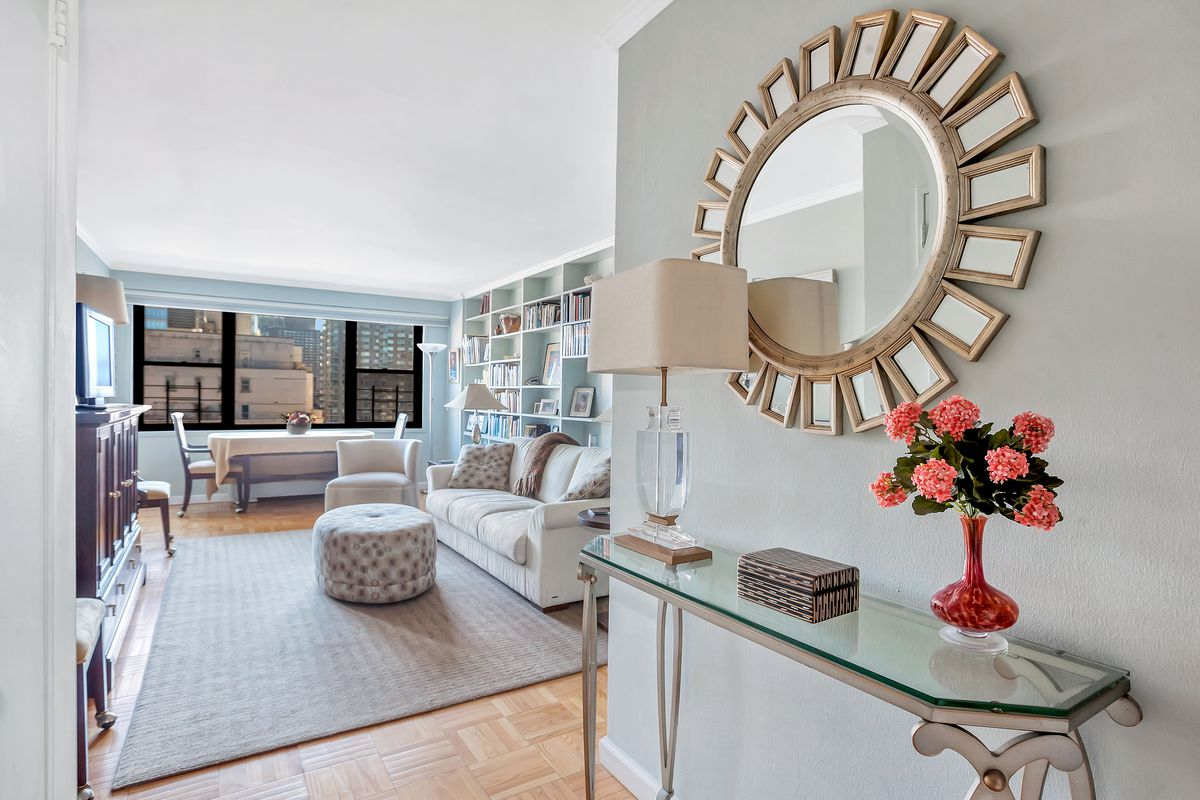 A foyer with grey walls, a glass table, a lamp, and a round mirror.