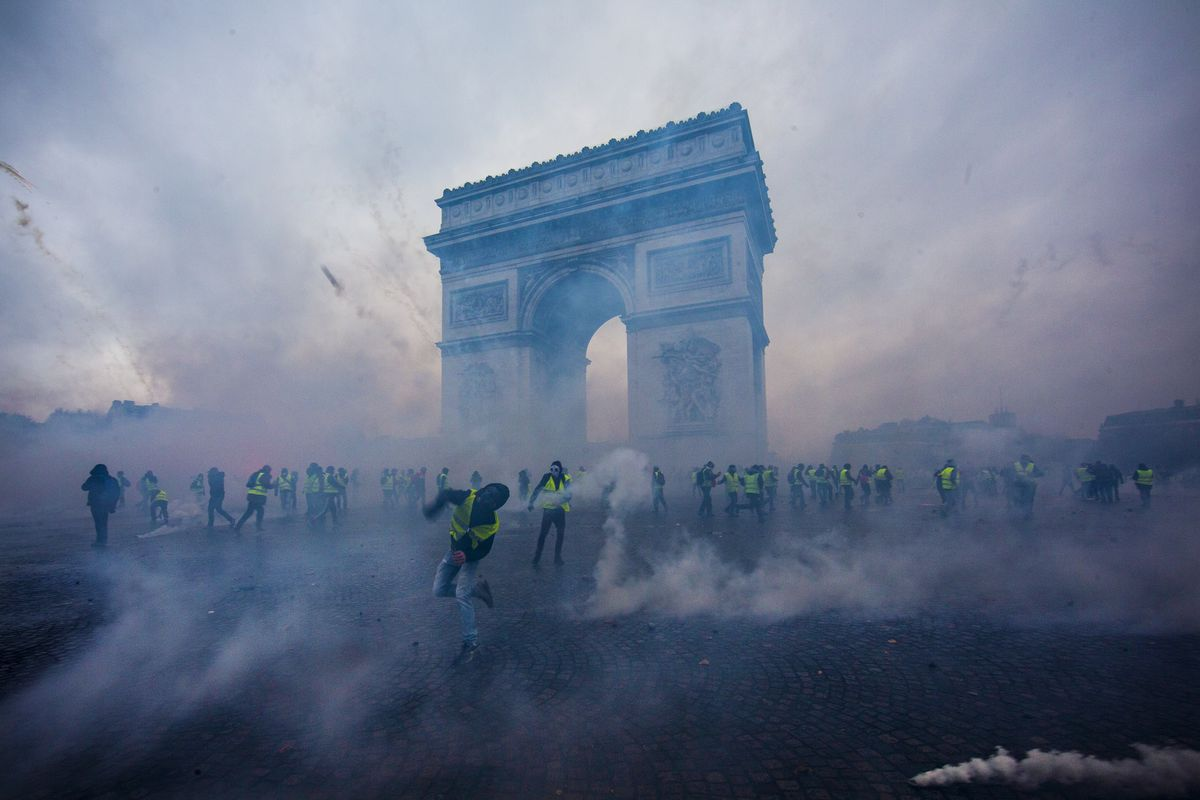 December 1: Teargas surrounds protesters as they clash with riot police during a 'Yellow Vest' demonstration near the Arc de Triomphe on in Paris, France. Read More. (Veronique de Viguerie/Getty Images)