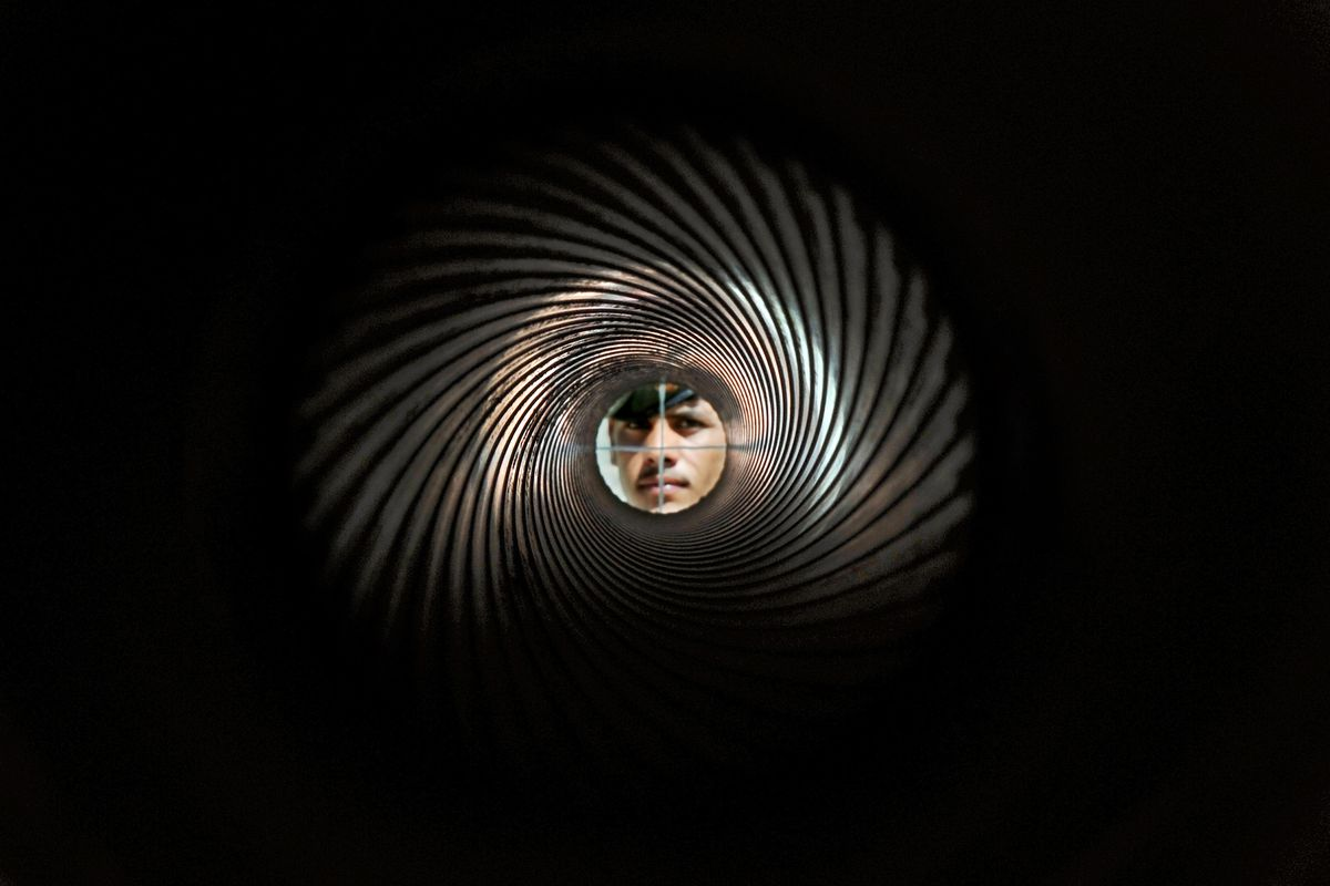 An Afghan soldier looks down the barrel of a D30 Howitzer.