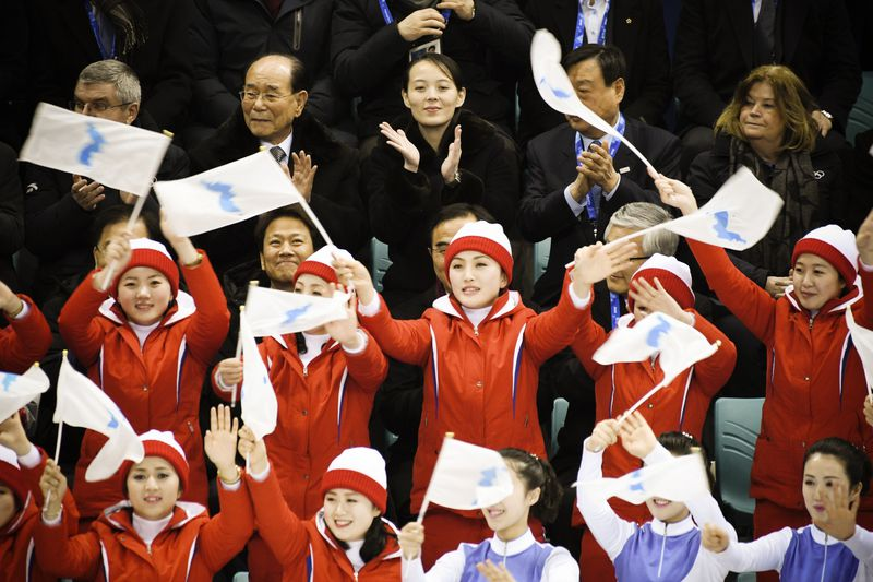 "North Korean leader Kim Jong Un""s sister Kim Yo Jong (top center), North Korea""s ceremonial head of state Kim Yong Nam (top second left) and IOC President Thomas Bach (left) sit behind North Korea""s cheerleaders waving the Unified Korea""s flags during the"