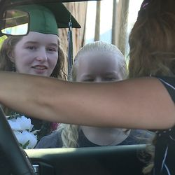 Deserae Turner visits with a well-wisher during a drive-by graduation celebration in her front yard in Amalga, Cache County, on Wednesday, May 27, 2020. Turner, who was shot in the head by two classmates in February 2017, graduated from Green Canyon High School Wednesday. Because of thecoronavirus pandemic, Turner was not able to receive her diploma in person.