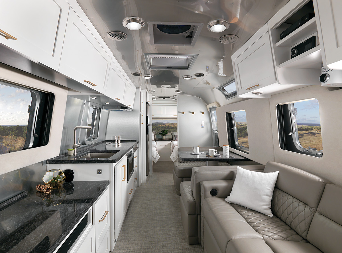 An interior view of the trailer has a gray couch on the right, and a kitchen with black countertops, white cabinets, and a sink on the left.