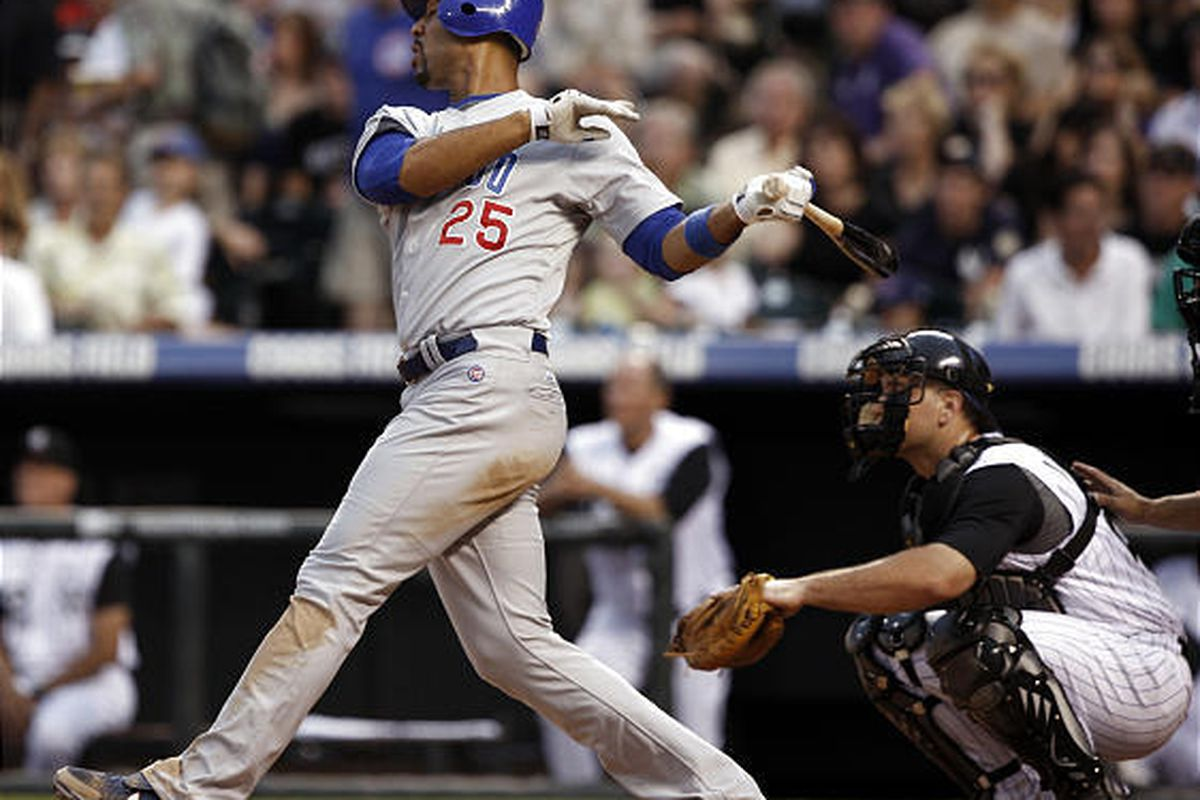Chicago Cubs' Derrek Lee, left, connects for a  solo home run as Colorado Rockies catcher Chris Iannetta looks on during  the fifth inning.