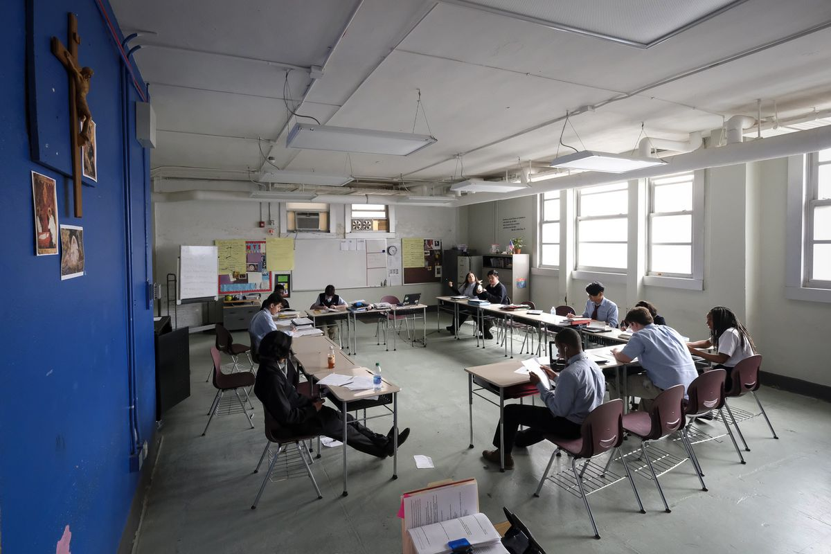 11 high school students look at papers and books while sitting at desks arranged in a large rectangle in an Indiana classroom. Pictures are pinned on a royal blue wall, and more pictures and posters are pinned to bulletin board on a far wall.