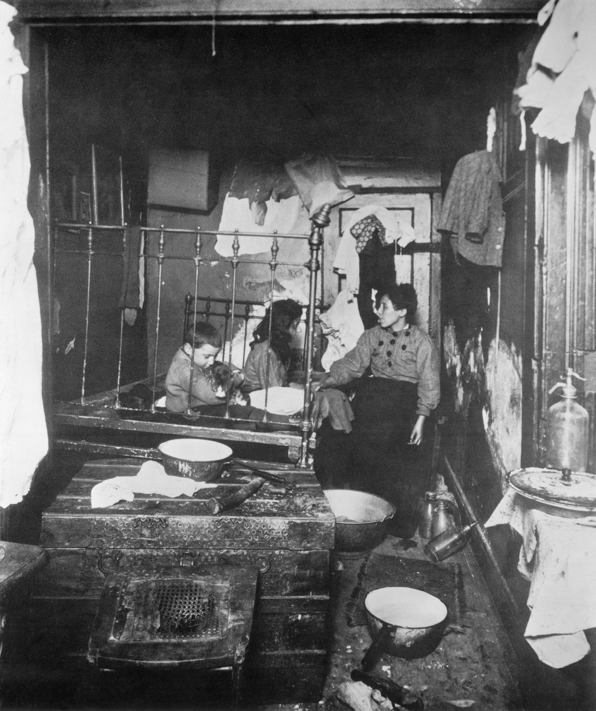 a black and white picture of a woman in children in a small, cramped room.