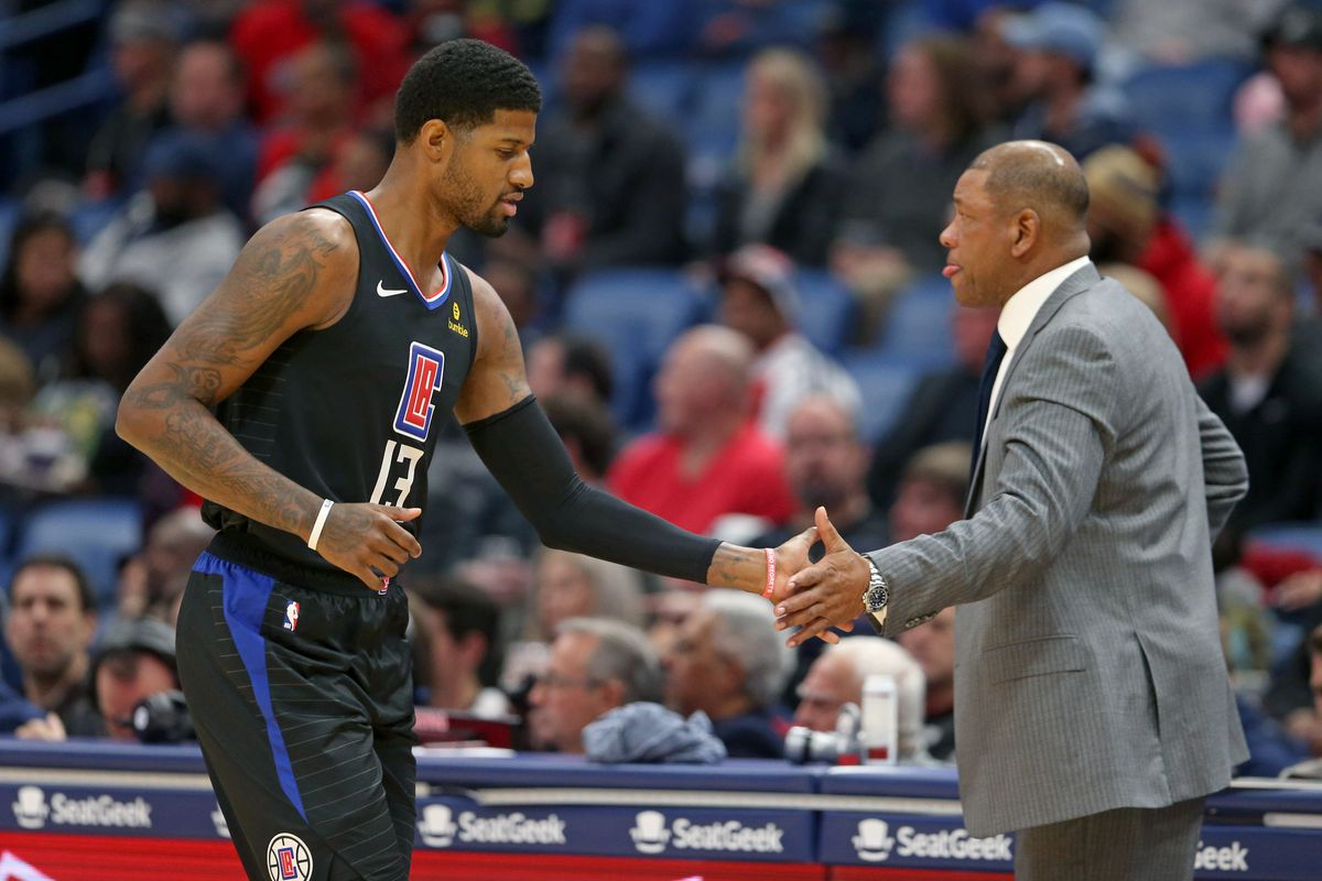 Los Angeles Clippers forward Paul George slaps hands with head coach Doc Rivers in the first quarter against the New Orleans Pelicans at the Smoothie King Center.