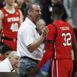 Utah head coach Larry Krystkowiak, left, confers with center Lahat Thioune who returns to the bench in the second half of an NCAA college basketball game against Colorado, Sunday, Jan. 12, 2020, in Boulder, Colo.