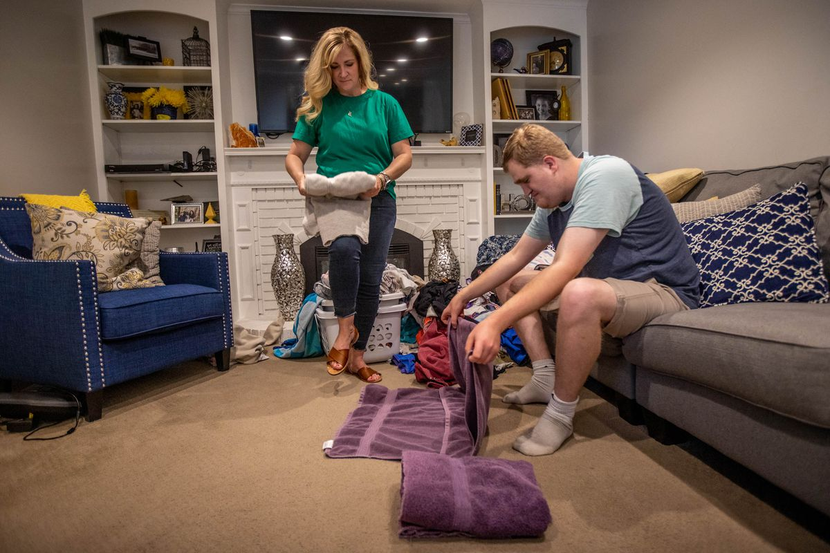 Jennie Dopp folds laundry with her son, Jackson, in their living room in Layton, Utah.