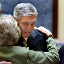Recently retired Jazz coach Jerry Sloan is hugged by Anna Kay Waddoups in the Senate at the Utah State Capitol on March 7, 2011. Sloan's wife, Tammy, looks  on.